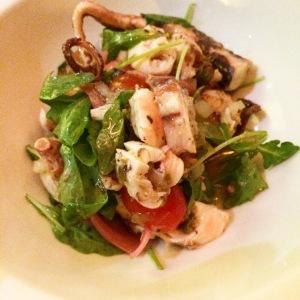 Salade de pieuvre avec oignons marinés au citron et chips de pommes de terre.
